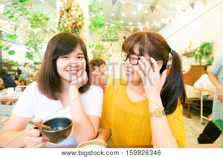 Smiling Female Asian Friends Holding Coffee Mugs While Talking Business