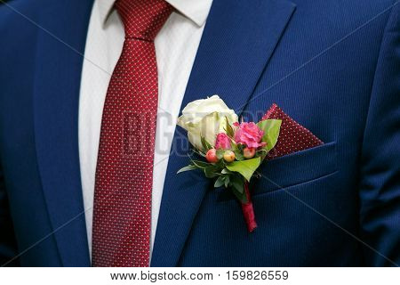 dark blue groom's suit and boutonniere of white and red roses and the handkerchief in the breast pocket