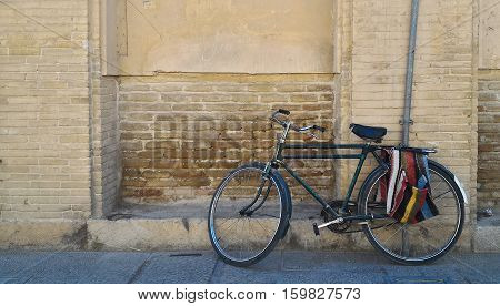 Classic style wall (yellow wall) lonely bicycle Part of old city in Iran Esfahan is the center city on the world map. Old bicycle parked in front of a rustic building