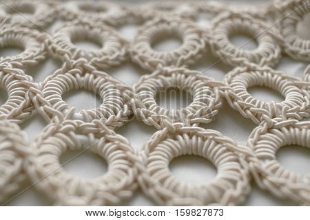 Close-up of braided cord pattern rings on white textured background. Selective focus.