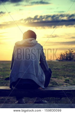 Toned Photo of Lonely Teenager sit on the Bench at Sunset Background