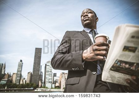 Confident businessman. Successful young man in full suit reading financial news on newspaper and drinking a cup of coffee