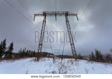 Electricity transmission power lines on winter background (High voltage tower). Metal electricity transmission pylon.