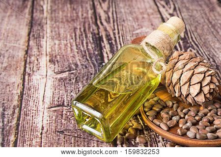 Cedar oil in a glass bottle and a cedar cones with nuts on a brown wooden plate.