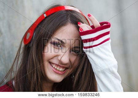 beautiful smiling teenager girl with piercing and make up listening music in headphones. Selective focus.