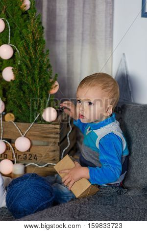 A Little Boy Sits By The Christmas Tree In Anticipation Of Holiday
