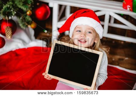 Little beautiful girl in a Santa Claus hat. Insert tex. Blackboard for text. New Year's holidays. Young girl celebrates Christmas