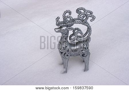 Figurine of Santa Claus reindeer Rudolph in snow