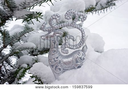 Figurine of Santa Claus reindeer Rudolph in snow on Christmas tree