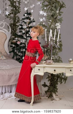 Portrait Of A Young Beautiful Blonde In A Red Dress At The Christmas Tree.