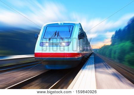 Scenic summer view of moving modern high speed streamlined passenger commuter train on tracks with motion blur effect