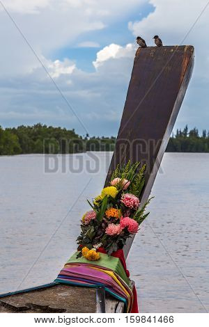 A longtail boat with two small birds and some flowers in a river