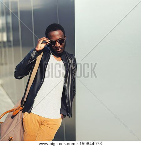 Fashion African Man Model Posing Wearing A Sunglasses And Black Rock Leather Jacket With Bag In The