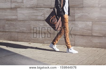 Fashion African Man In Black Rock Leather Jacket With Bag Walking Over Grey Textured At Evening City