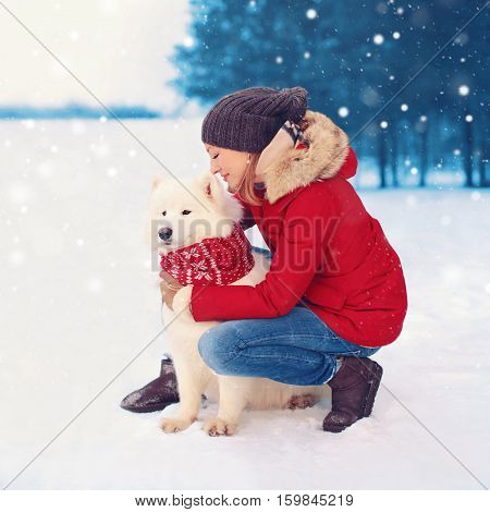 Happy Woman Owner Embracing White Samoyed Dog In Winter Christmas Day
