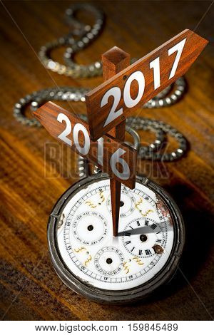 New Year 2017 - Old pocket watch with two wooden signs with arrows and the years 2016 and 2017