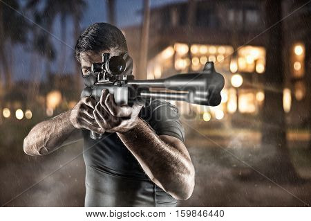 man in black military uniform and headgear aiming with rifle under the rain on night city background