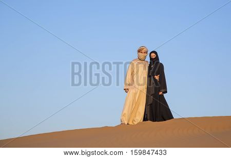 Couple in traditional clothing in a desert near Dubai