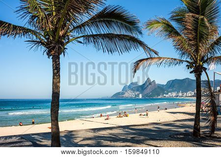 Rio de Janeiro Brazil - July 24 2016: Tourists and active residents are in the Ipanema Beach and front street with palms and mosaic of sidewalk in the sunny morning