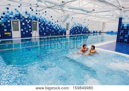 two young beautiful brunette girls in swimming pool indoors.