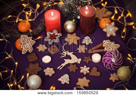 Christmas Gingerbread Cookies With Toys, Cinnamon, Tangerines, Candles, Festoon Lights On Purple Bac