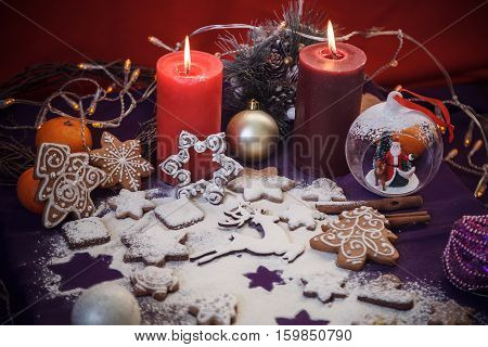 Christmas Gingerbread Cookies With Flour, Toys, Cinnamon, Candles, Festoon Lights On Purple Backgrou