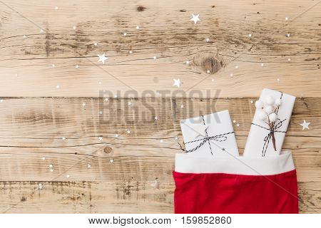 Top view on nice Christmas gifts wrapped in white gift paper Christmas tree decorations in Santa's hat on wooden background with sparkling stars. New Year holidays and celebration concept