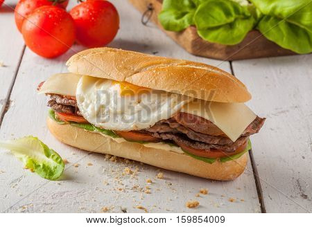 Chivito is a typical sandwich from Uruguay with lettuce tomato bacon beef fried or boiled eggs and cheese.