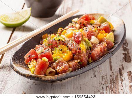 Hawaiian tuna poke with mango avocado onion and sesame seeds.