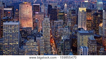 Lights come on in Midtown Manhattan in the early evening