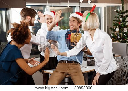 Happy cheerful colleagues celebrating christmas party in office smiling giving presents.