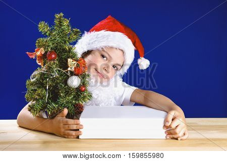 A little boy dressed as Santa Claus is smiling happily peeping from behind the Christmas tree hugging his Christmas gifts. Looks into the camera. Gift in a white box. On a blue background. Close-up.