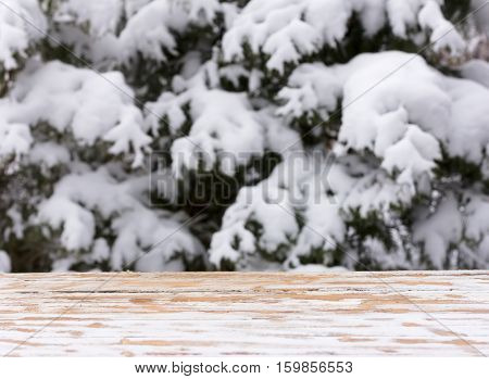 empty wooden table on a background of snow-covered trees. for product display montage