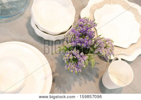 decorated table with white crockery and with a bouquet of flowers