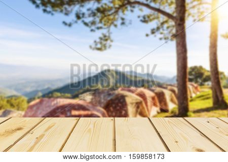 Wooden board empty table in front of blurred background of tent for camping in the mountain with pine trees and sea of fog and flare used for mock up for display or montage your products vintage.
