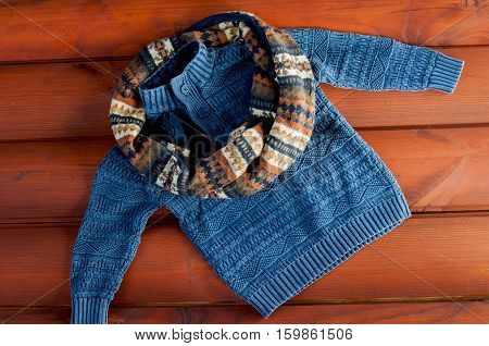 flat lay children's winter clothing. blue sweater with scarf on wooden background.
