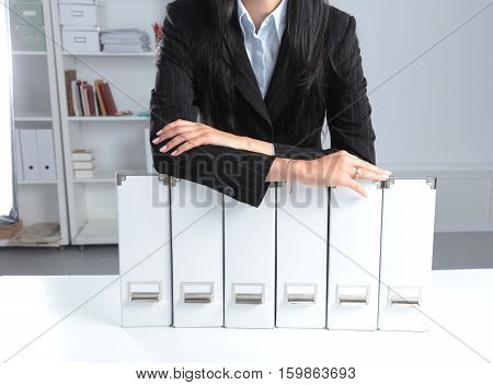 businessman holding data files on binder shelves background.