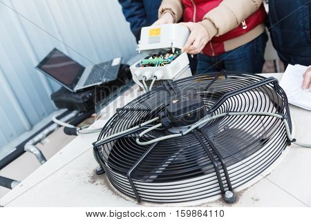 Cooling of industrial air conditioners, fans on the condenser. Engineer repairing a condenser fan control unit.