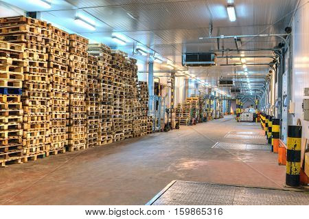 Saint-Petersburg Russia - October 31 2016: Empty wooden euro pallets stacked inside distribution warehouse loading dock.
