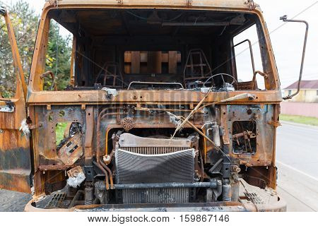 truck completely burned on the roadside, rusty cabin and car parts closeup