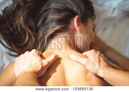 Couple and lovely moments in the bed - Close up of boyfriend giving massage for his beautiful girlfriend relaxing in a bed whit white sheets - Focus on hand