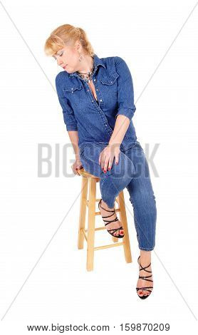A lovely blond woman in jeans and jeans jacket sitting on a bar chair looking to the site isolated for white background.