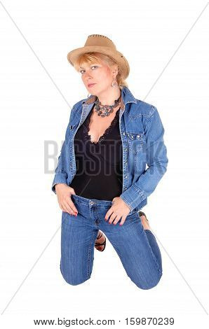 A pretty woman in jeans pants and jeans jacket kneeling on the floor wearing a cowboy hat isolated for white background.