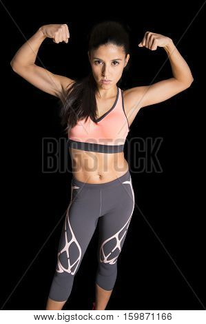 young attractive latin sport woman posing in fierce and badass face expression with fit slim body isolated on black background in healthy lifestyle and fitness concept