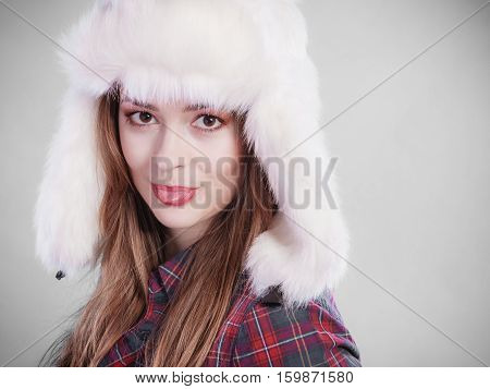 Young woman wearing fluffy cap. Teenage make silly face cold time.