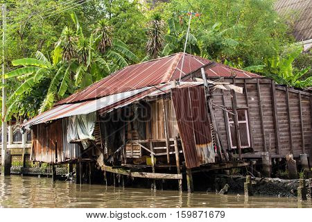 Shanty house in Bangkok water canals along the river banks, Thailand