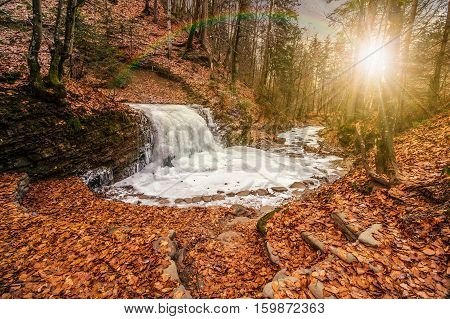 Frozen Waterfall In Forest At Sunset
