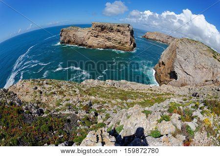 Fisheye view of scenic rocks in the ocean near Cabo de Sao Vicente Cape in the Algarve Portugal