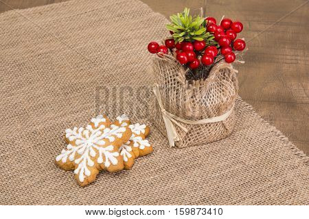 Two sticks with Christmas pattern, viburnum in a vase of scrim.