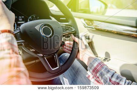 Woman wearing holiday vintage shirt changing cruise control settings while driving on UK highway - driving left hand drive